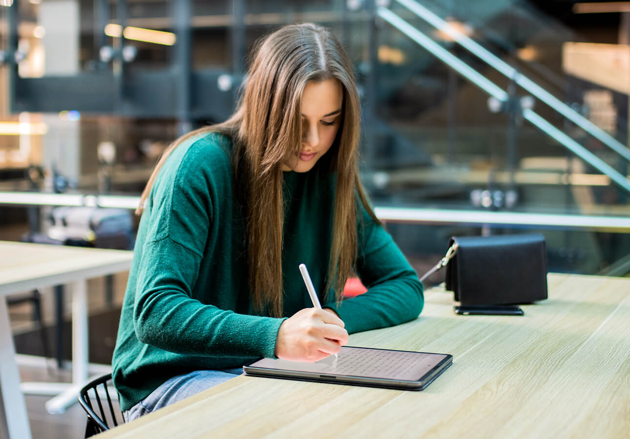 A college student takes notes using an iPad and Apple Pencil.