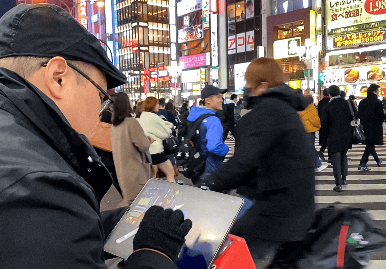 Rob Sketcherman stands in a crowded city square while sketching on his iPad.