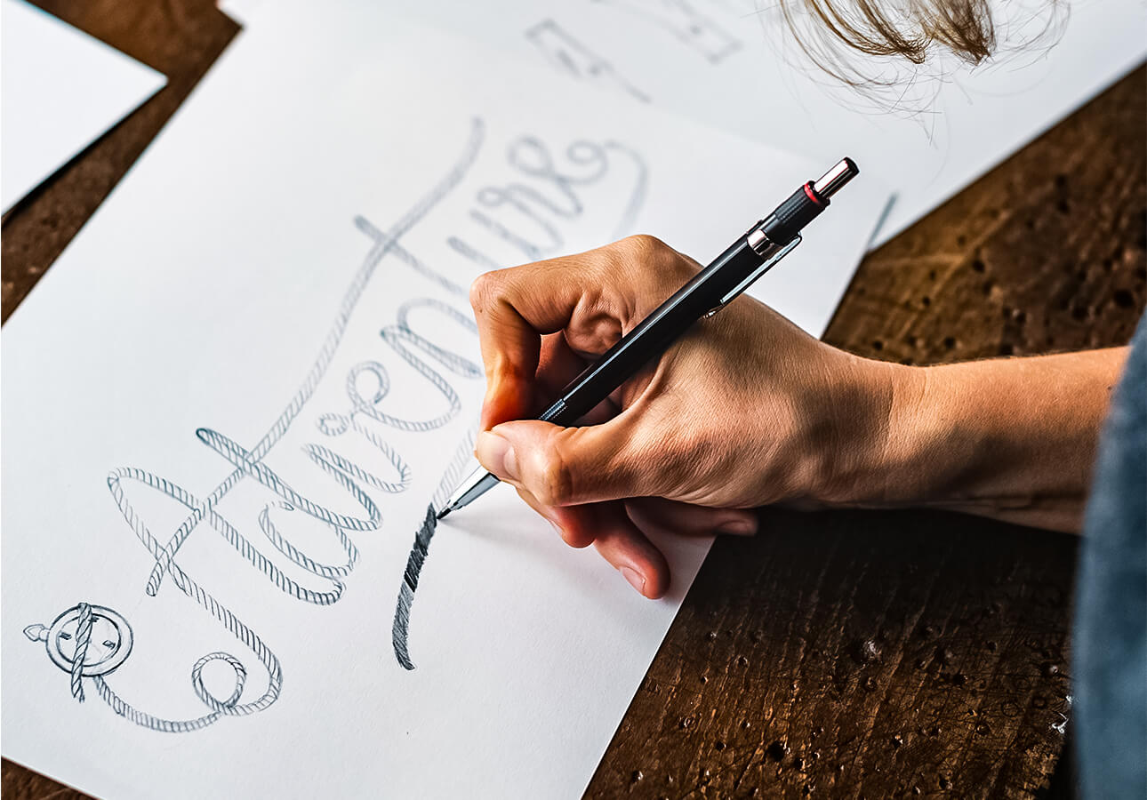 A person doing a hand lettering sketch.