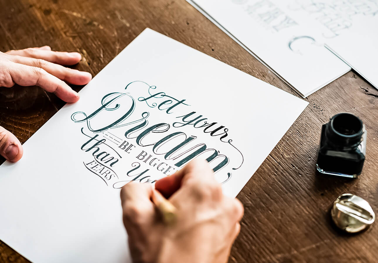 A person working on a hand lettering piece using ink.