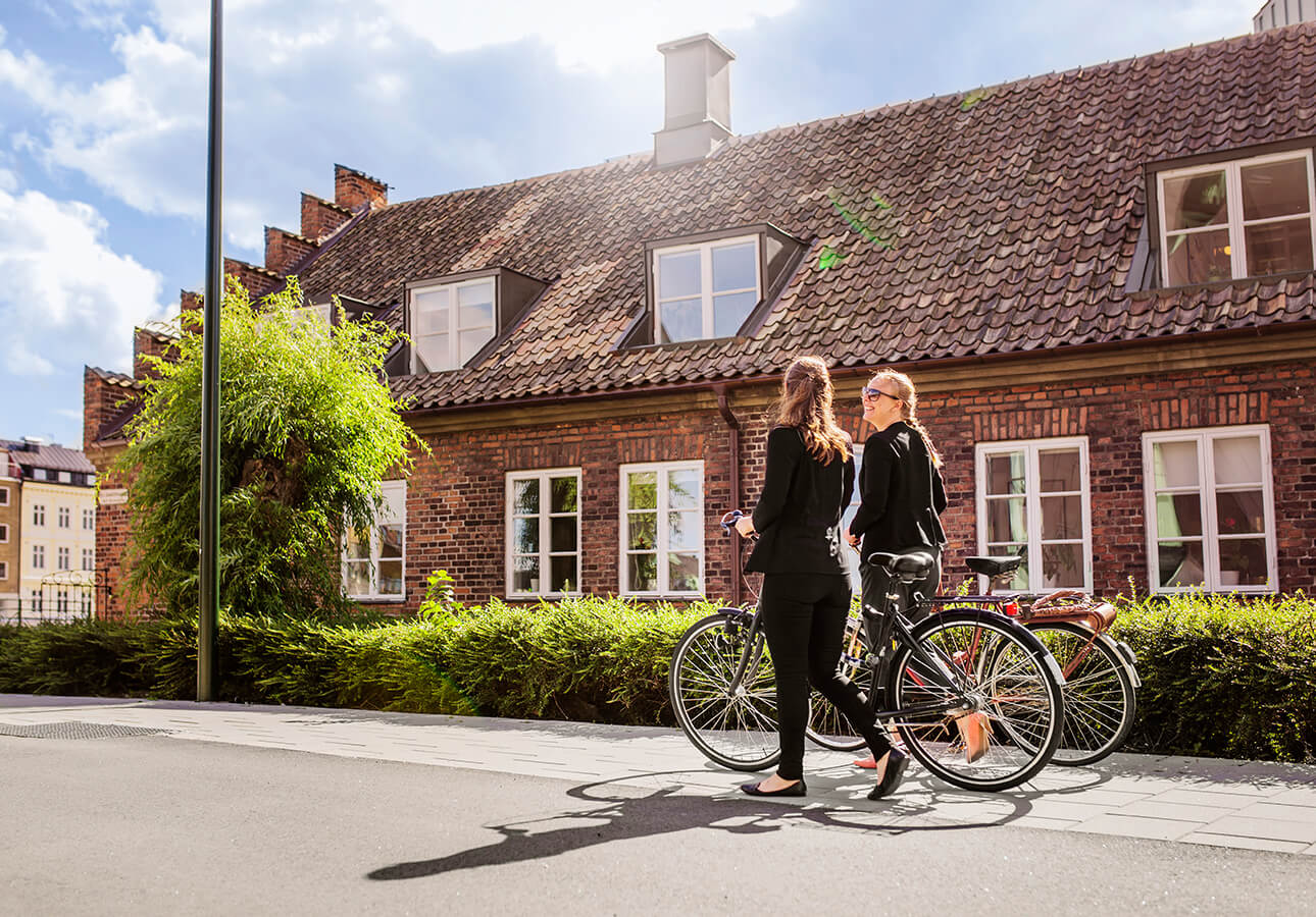 Two people walking with their bikes in a town on a sunny day.