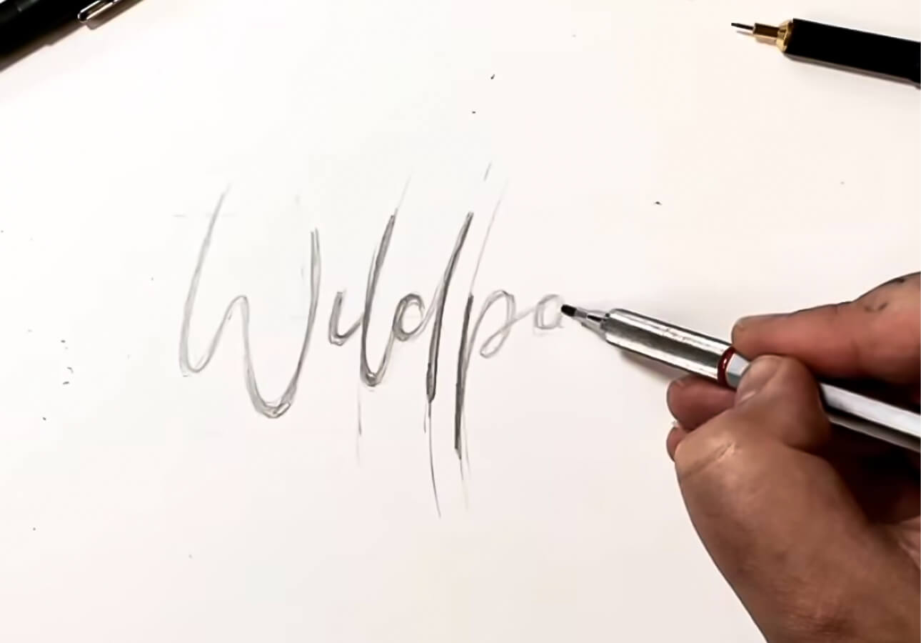 An image depicting an artist working on a hand lettering sketch.