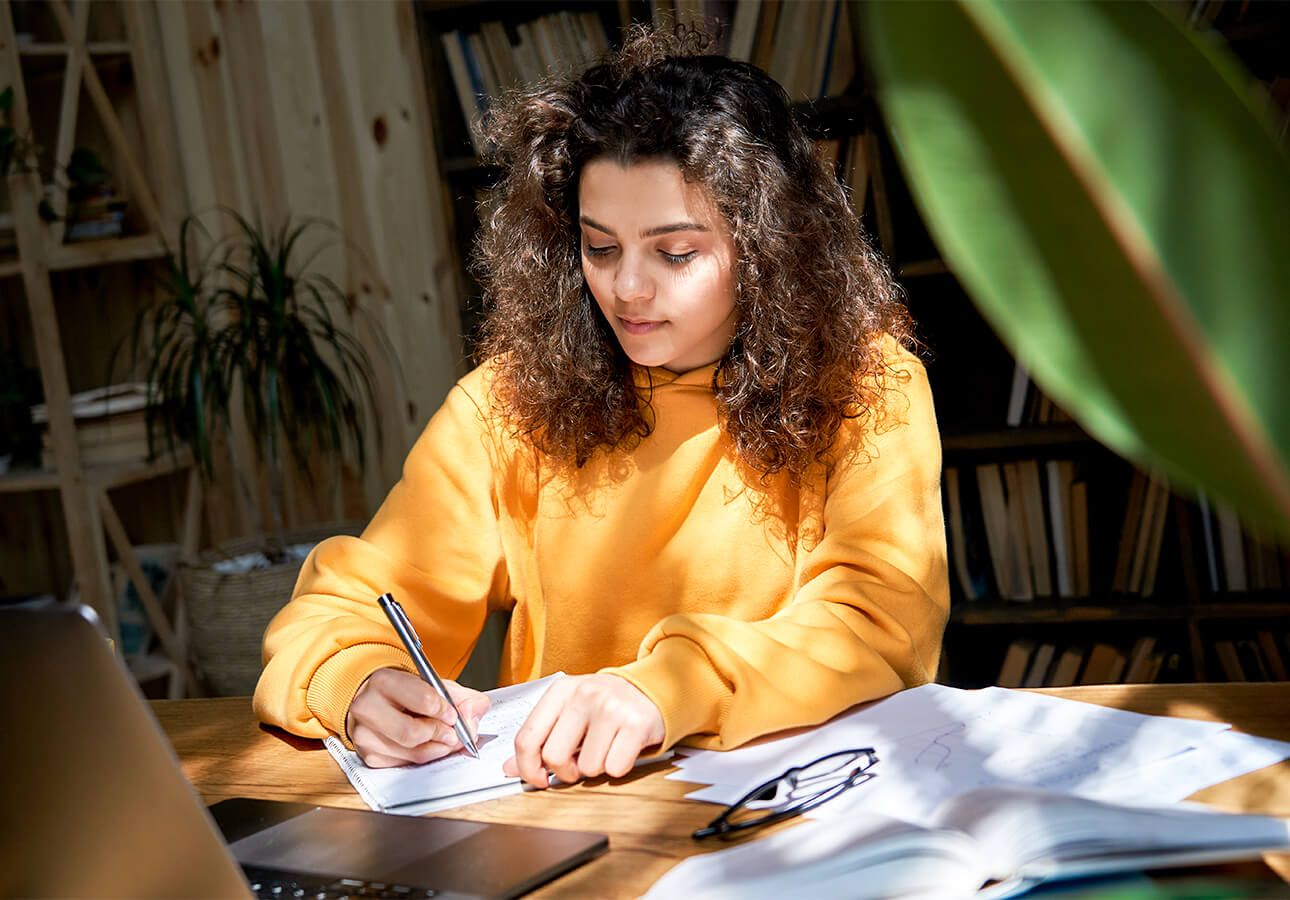 An young woman surrounded by books and a laptop takes notes using a notebook and pen.