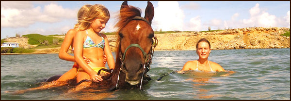 kids riding a horse in water