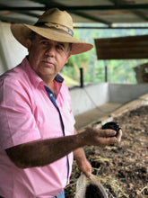 Jose Humberto Gonzalez holding a fermented orange used in his coffee fermenting process
