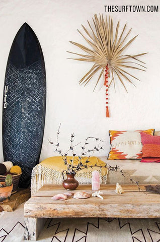 Tabla de surf azul decorando un salon estilo boho