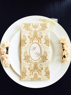 Stunning golden/ivory wedding invitation with tassel.