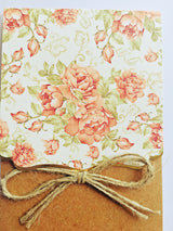 Floral and kraft brown wedding invitation with ribbon.
