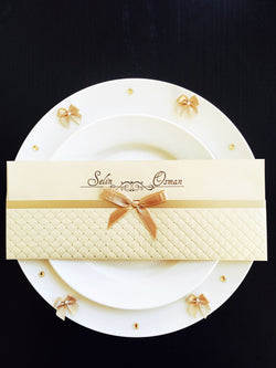 Stunning ivory and gold wedding invitation with ribbon.