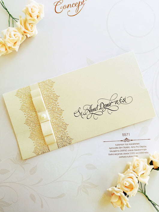 Ivory and gold wedding invitation with ribbon.