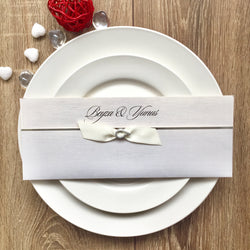 Elegant white and silver wedding invitation with ribbon.