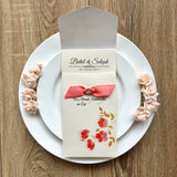 Vintage style wedding invitation with flowers and ribbon.