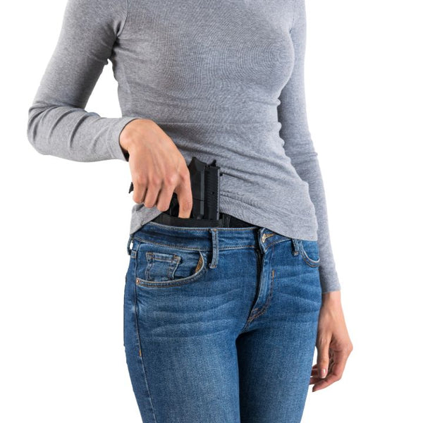 Woman gripping on weapon with inside the waistband holster