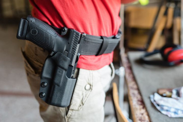 Man gripping on weapon with outside the waistband holster