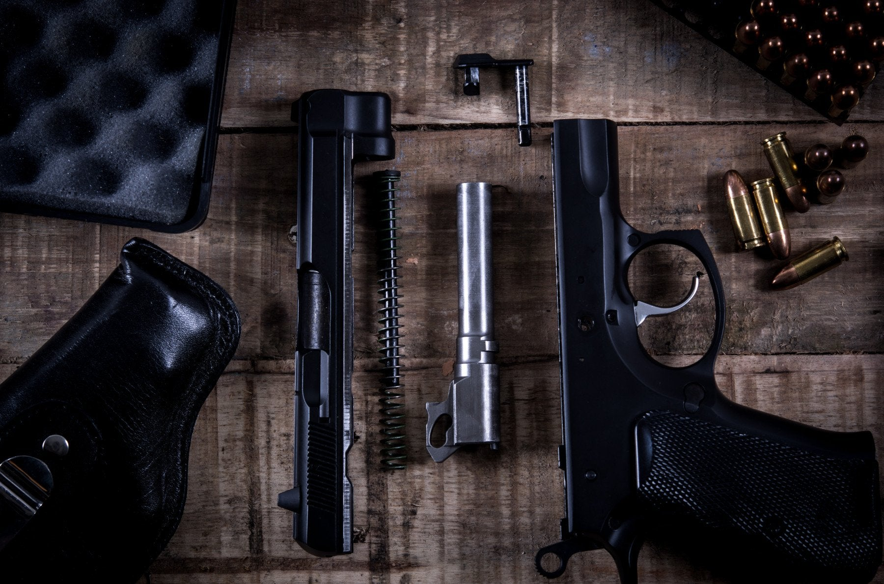 Gun taken apart on a table for cleaning