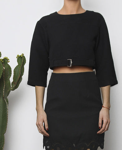Bella London Black cropped top with boxy fit, front silver buckle fastening and ¾ sleeves. Close up front photo.