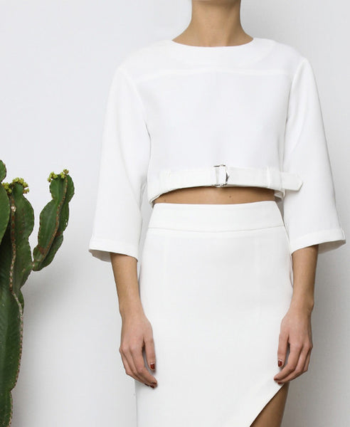 Bella London White cropped top with boxy fit, front silver buckle fastening and ¾ sleeves. Close up front photo.