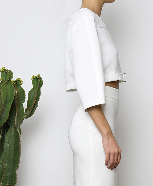 Bella London White cropped top with boxy fit, front silver buckle fastening and ¾ sleeves. Close up side photo.