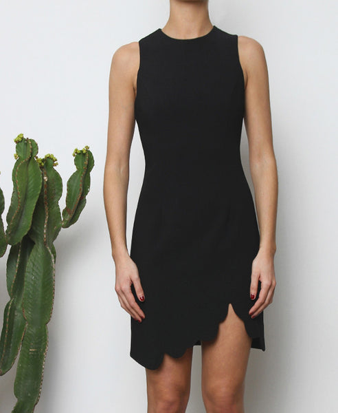 Bella London Augi Little Black Dress with asymmetric scalloped hem and a slight leg slit. Close up front photo.