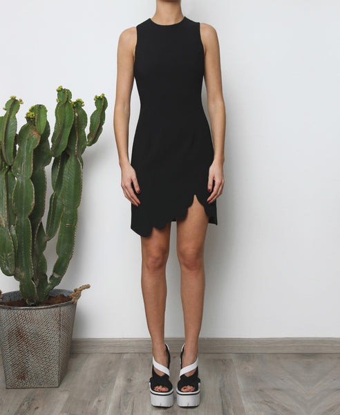 Bella London Augi Little Black Dress with asymmetric scalloped hem and a slight leg slit. Full length front photo.