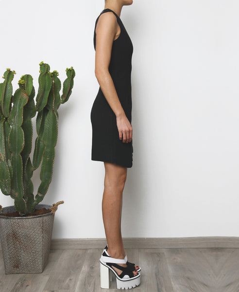 Bella London Augi Little Black Dress with asymmetric scalloped hem and a slight leg slit. Full length side photo.