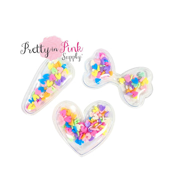 Pastel rainbow hearts clay slices filled shakers in heart shape, bow shape, and clip cover shape.