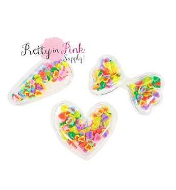Candy Heart clay slices filled shakers in heart shape, bow shape, and clip cover shape.