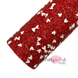 Rolled red chunky glitter sheet with white sliced clay hearts.