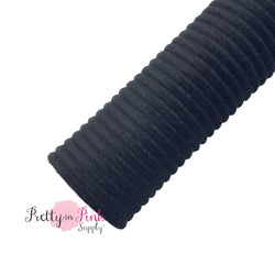 Rolled black velvet textured stripe fabric sheet.