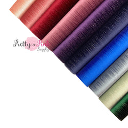 Rolled group photo of silver streak velvet sheet in light pink, pink rose. wine, dusty mauve, purple, navy, royal blue, grey, sage, and emerald.