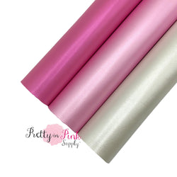 Rolled group photo of pink, light pink, and off white, smooth faux leather polished pearl sheets.