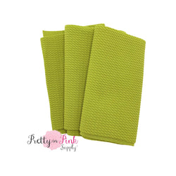 Folded over solid avocado color textured, stretch liverpool fabric strip.