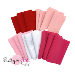 Folded liverpool fabric strips in red, pale pink, light pink, white, and hot pink.