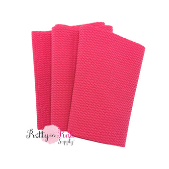 Folded over solid hot pink color textured, stretch liverpool fabric strip.