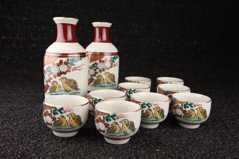 Vintage Japanese Kutani-yaki sake set in red, green and yellow with flower and bird pattern
