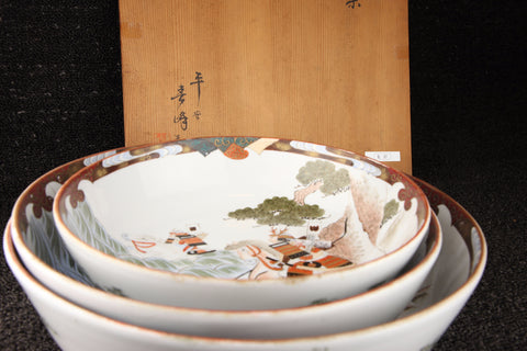 Vintage Japanese Kutani-style painted nesting bowls in red, brown, and green with landscape pattern