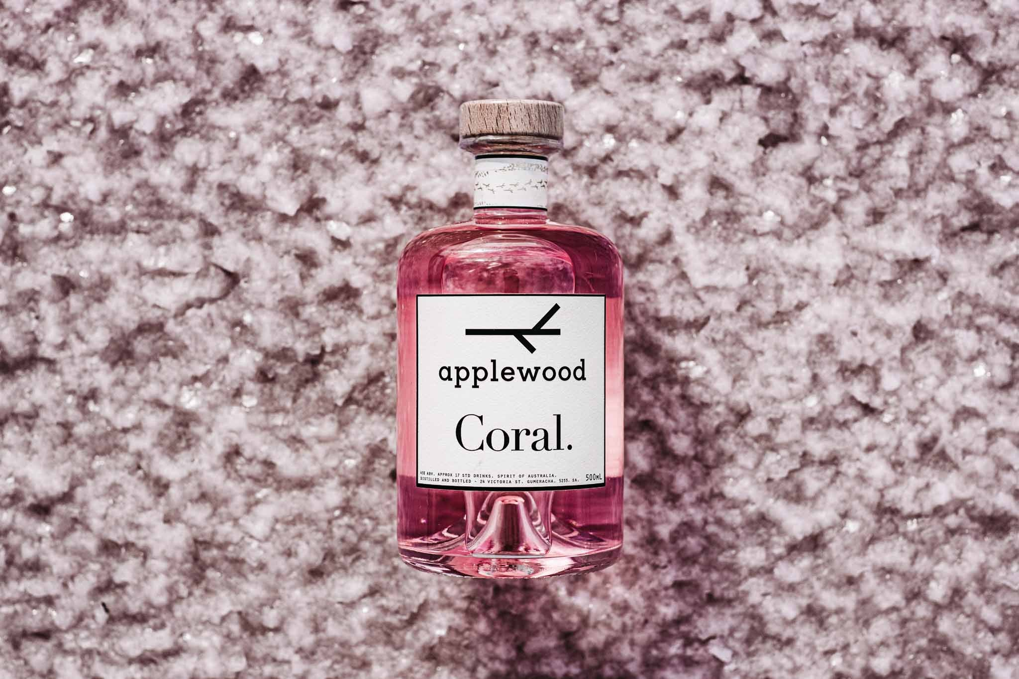 coral pink gin is laying down on a salt lake. the shot is from above showing the beautiful pink colour of the gin.