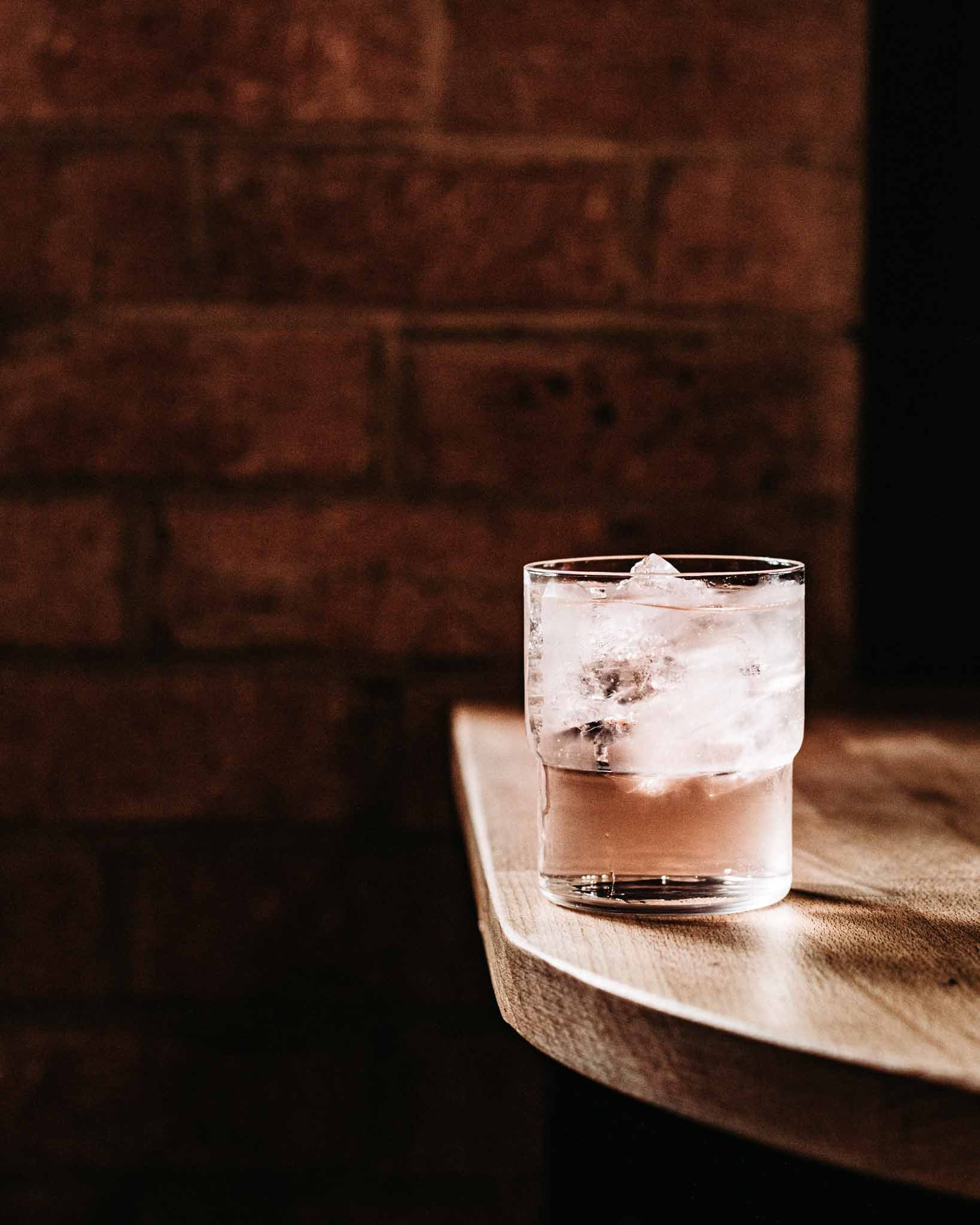 pink gin in a glass with tonic water and lots of ice sits on a table in Applewood bar