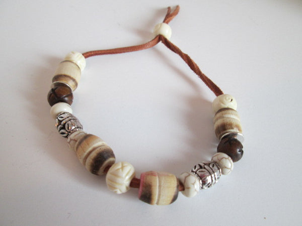 Beautiful leather bracelet featuring wooden beads, bone beads, and silver colored metal beads. - SpuzzosDeals