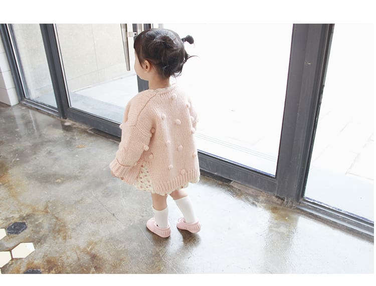 a little girl standing in front of a window