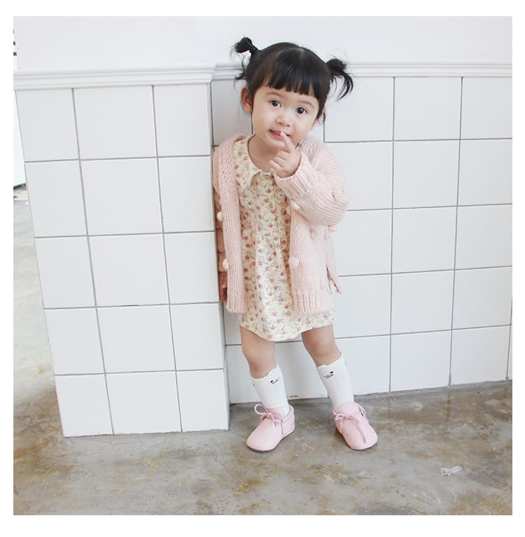 a little girl standing in front of a tiled wall