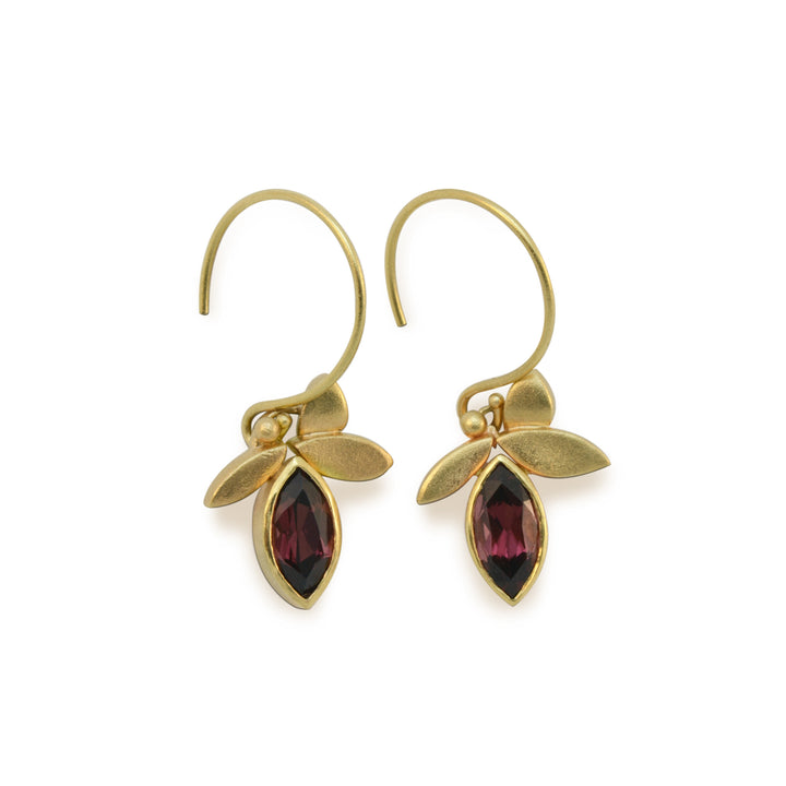 14kt yellow gold earrings with a 3 leaf design have 2 bezel set,  5mm x 7mm marquise cut responsibly sourced dark red Rhodolite Garnets. Earrings are 1.25