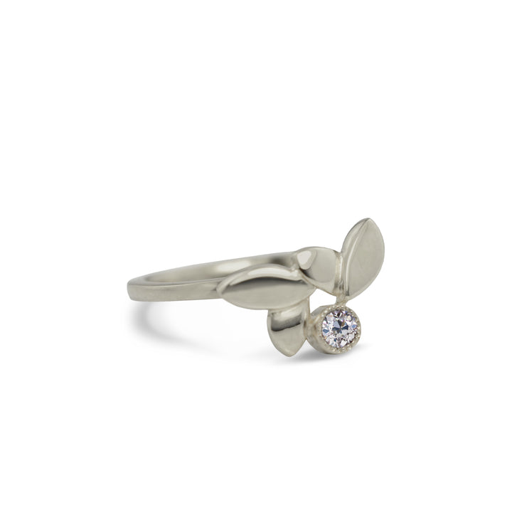 Modern organic women's ring with 3 leaves made from 14kt recycled white or yellow gold. Also available in Fairmined gold. A 3mm round white recycled diamond is bezel set on the side.