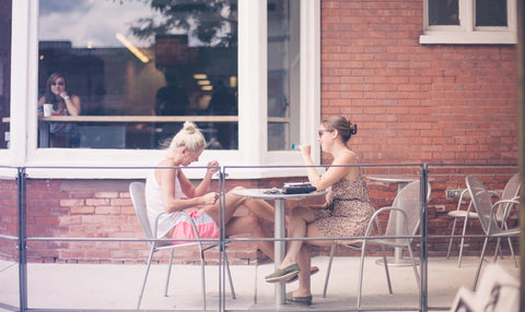 2 girls talking at a table