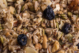 Close-up shot of Coco, Bee & Nut: Blueberry Lemon grain free granola. Yellow flecks of dried, powdered lemon lightly coat the oven-baked mix of cashew pieces, walnut and almond pieces, sunflower seeds, pumpkin seeds, small coconut flakes, chia and flax; highlighted by plump dried blueberries.