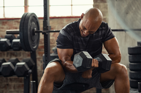 Man doing a one-armed tricep curl with a dumbbell