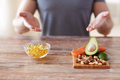 bowl of fish soft gels oil and high protein food on a cutting board