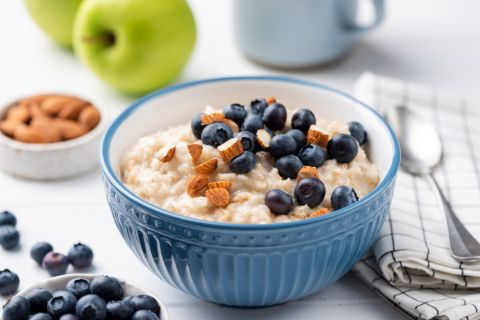 Blue bowl of oatmeal topped with almonds and blueberries