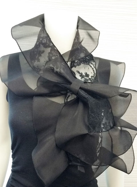 "Lace scarf with organza ruffle and loop closure for easy adjustment; available in black, white, cream, or black with pink ruffle;  measurements: 45"" x 11"""