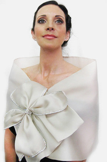 A cream  satin faced organza bridal bow wrap with rhinestone bow trimmings and snap closure;